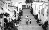 A grandmother with her grandson walking back from the beach along a street lined mobile homes in Briny Breezes, 1992.